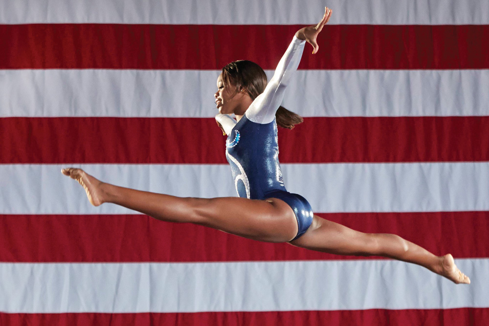 Two-time Olympic gymnast gold medalist, Gabrielle Douglas flying through the air. Photograph by Allen Fraser