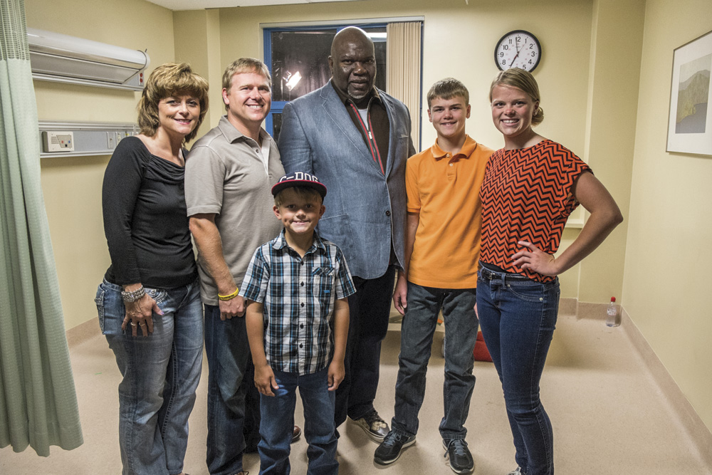 The Burpo family — (l to r) Sonja, Todd, Colby, Colton and Cassie — surrounding Heaven is for Real producer, Bishop T.D. Jakes. Photograph by Allen Fraser