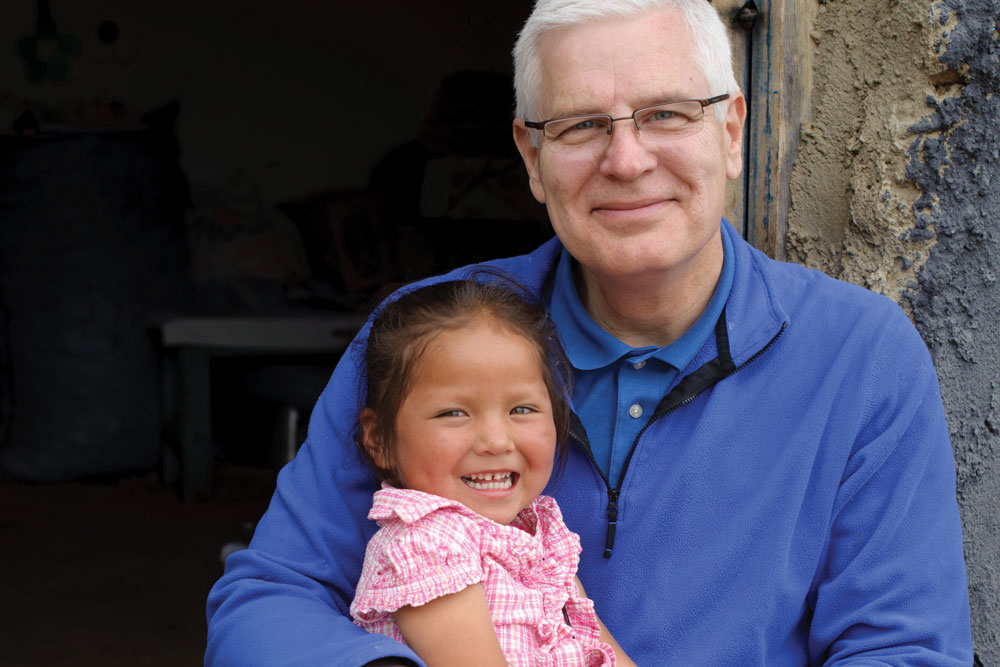 Rich Stearns holds sponsored girl, Nathaly, 3, on his lap, in Tiraque, Bolivia.