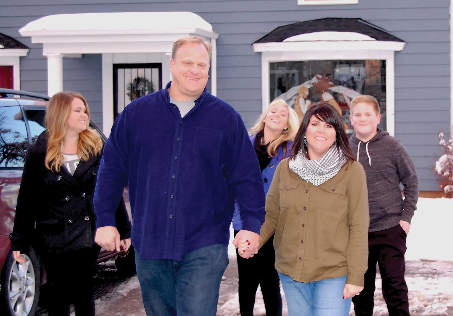 Russ holding hands with his wife Tammy.  Their three kids behind them: Allie, Katelyn, and Jack.